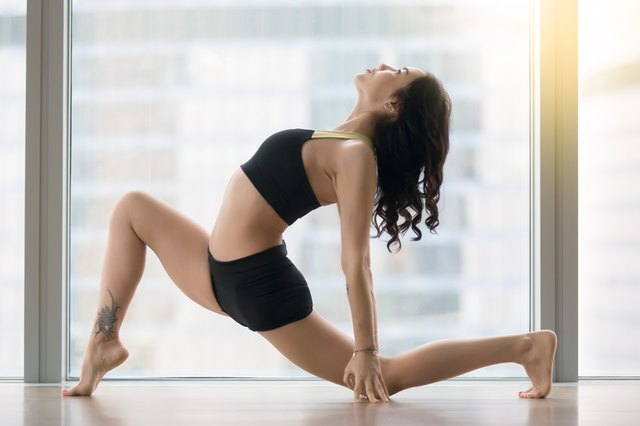 Young attractive woman in anjaneyasana pose against floor window, profile