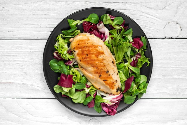grilled chicken breast with mixed salad on a black plate with knife and fork