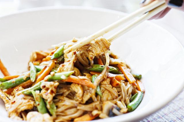 Woman's hand uses chopsticks to serve Thai chicken noodle dish