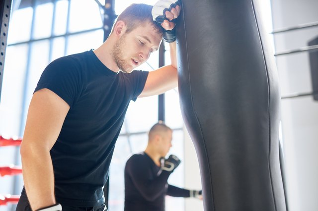 Exhausted boxer leaning on punching bag