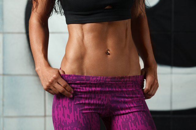 Fitness sexy woman showing abs and flat belly. muscular girl