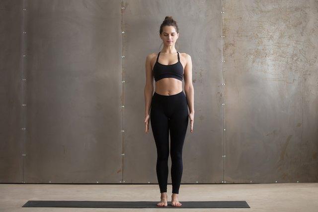 Young attractive woman standing in Tadasana pose, grey studio ba