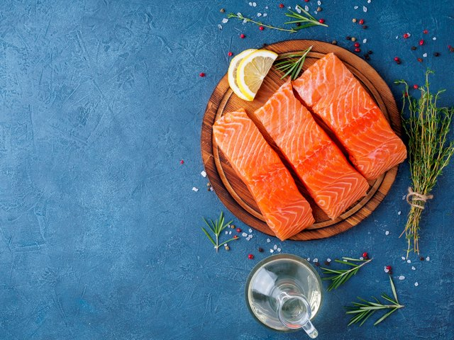 Food background, sliced portions large salmon fillet steaks on chopping board on dark blue concrete table, copy space, top view
