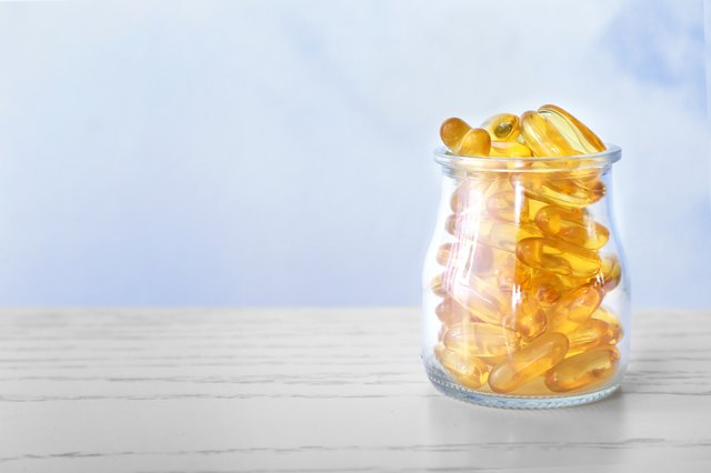 Glass jar with fish oil capsules on table