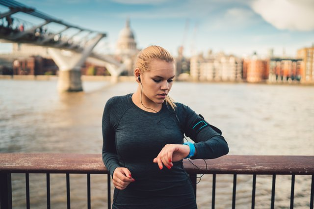 Sportswoman in UK checking pulse on smart watch during workout