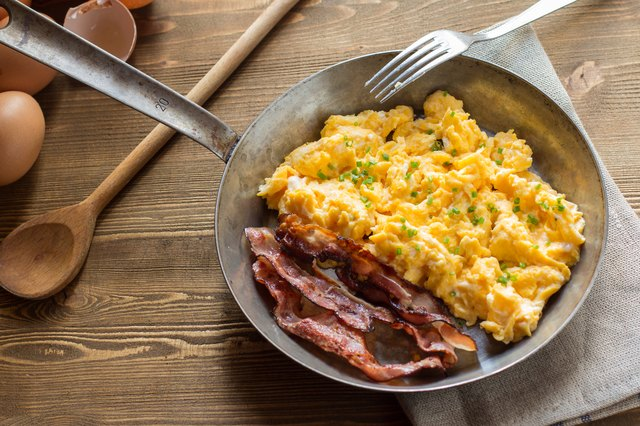 Scrambled eggs with bacon in frying pan