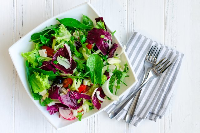 Fresh summer green salad mix on a wooden table