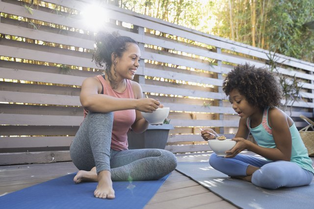Mother and daughter eating cereal on yoga mats on deck