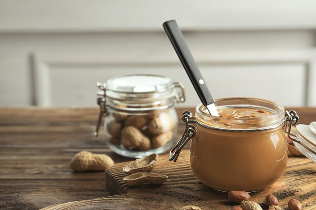 Glass jar with peanut butter on kitchen table