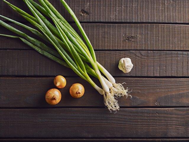 Fresh leek, onion and garlic on a wooden background