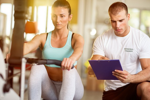 Trainer taking notes on attractive woman working out