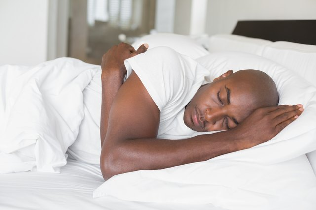 Peaceful man sleeping in bed