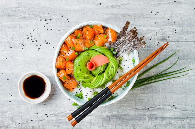 Hawaiian salmon poke bowl with seaweed, avocado rose, sesame seeds and scallions