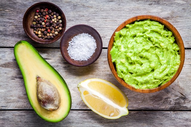 ingredients for homemade guacamole: avocado, lemon, salt and pepper