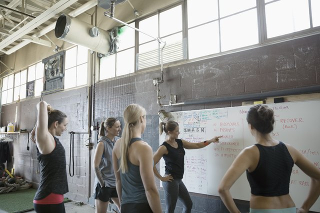 Female instructor and gym students at whiteboard in gritty gym