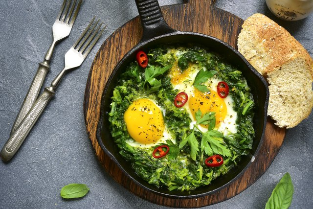 Green shakshuka in a cast iron pan