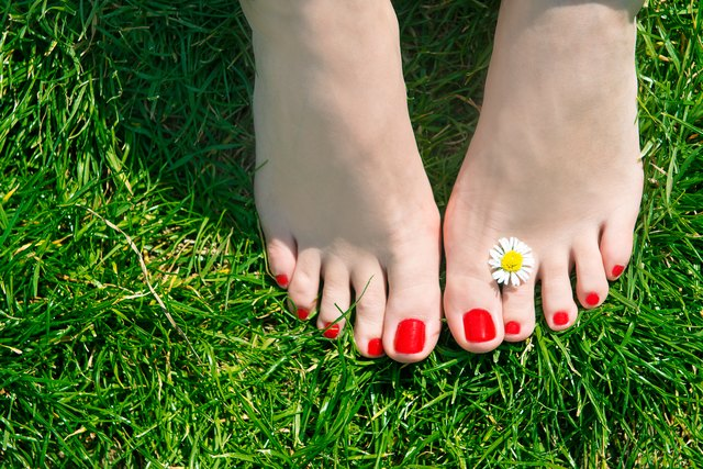Woman feet with pedicure and flower on green grass
