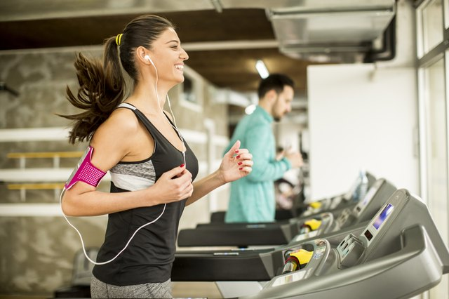 Young woman running on the treadmill and listening to music at the gym