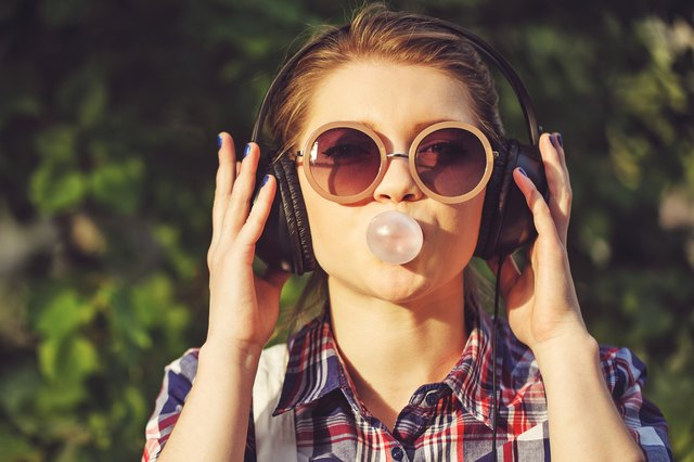 Hipster girl listening to music on headphones and chews cud.