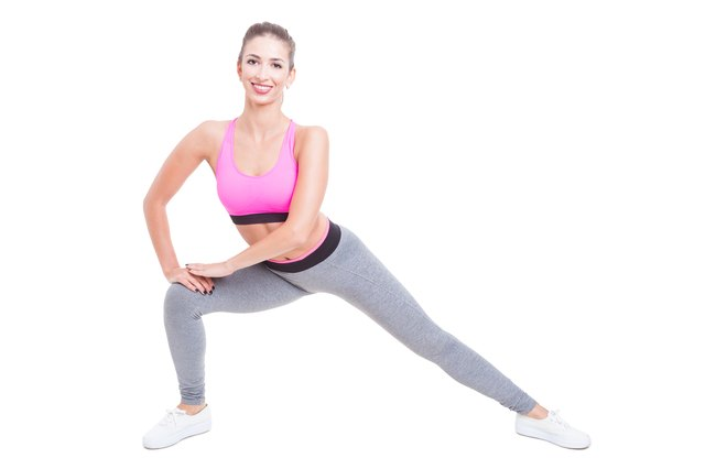 Female trainer making side lunges and smiling