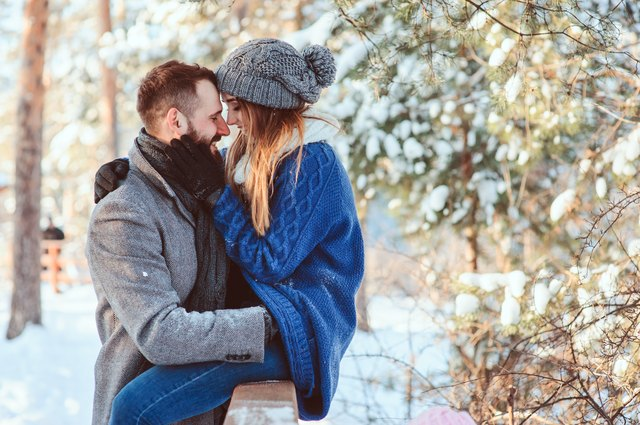 happy loving couple walking in snowy winter forest