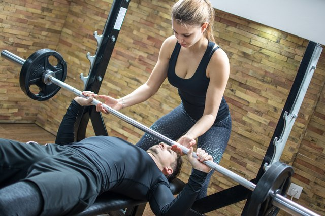 Sporty couple exercising together in gym. Handsome young man lifting weights with assistance of his attractive girlfriend in fitness club.