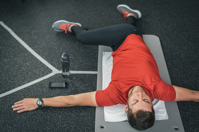Sporty man stretching back before gym workout indoor on mat