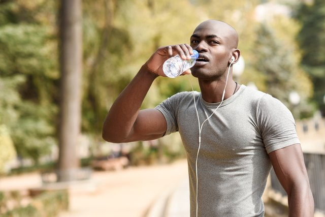Young black man drinking water before running in urban background