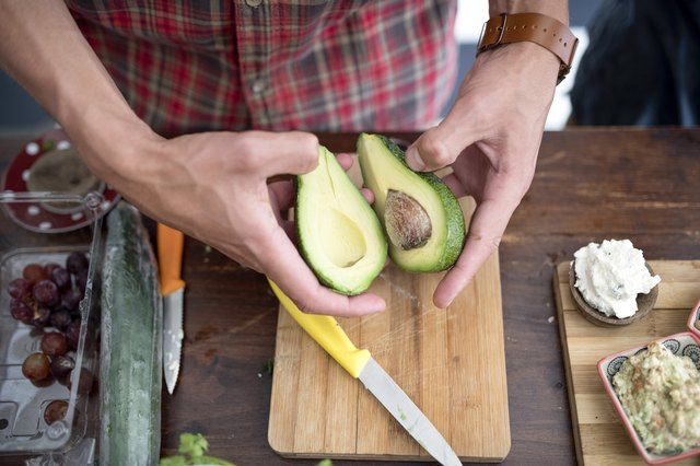 Young man holding halves of avocado in kitchen