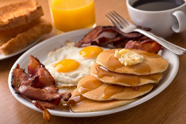 Breakfast with bacon, eggs, pancakes and toast