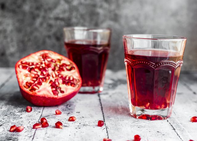 Glasses of pomegranate juice and sliced pomegranate
