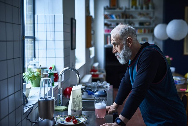Tired looking senior man leaning on kitchen counter with sports drink