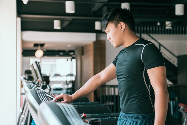 Male runner set up treadmill in gym