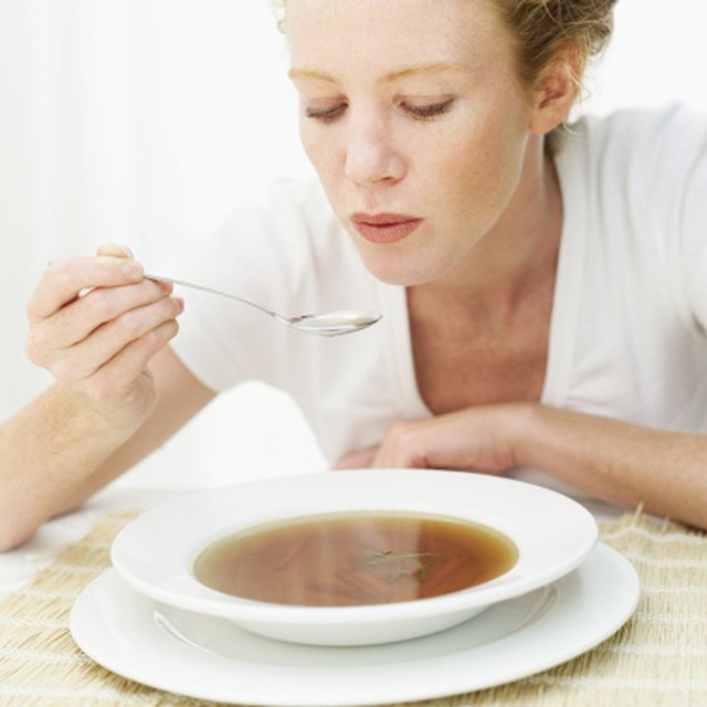 Young woman blowing a spoonful of hot soup
