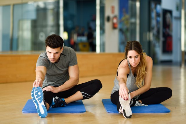 Two people streching their legs in gym.
