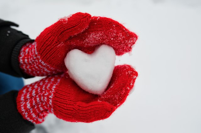 red female gloves hold a white heart from the snow