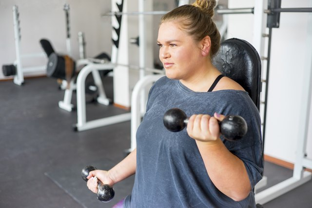 Woman doing arm workout l in a gym