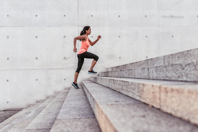 latina sports woman running up outdoor stairway in berlin
