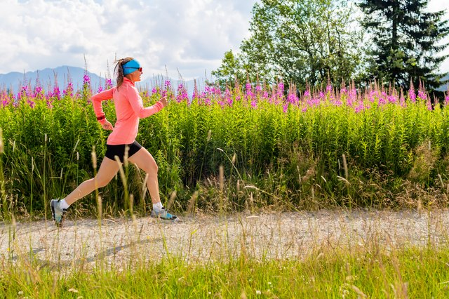 Young woman running on country road in mountains, summer day