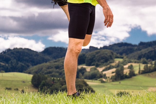 Male runner stretching outdoors at mountains background