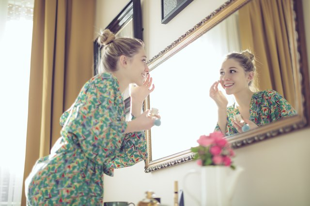 Young woman applying aloe vera gel to her face