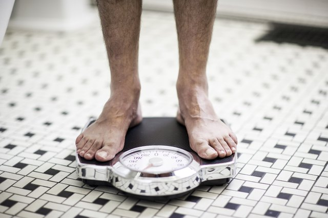 Adult man on bathroom scales.
