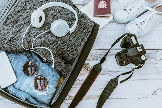 Open suitcase with casual female clothes ready to travel