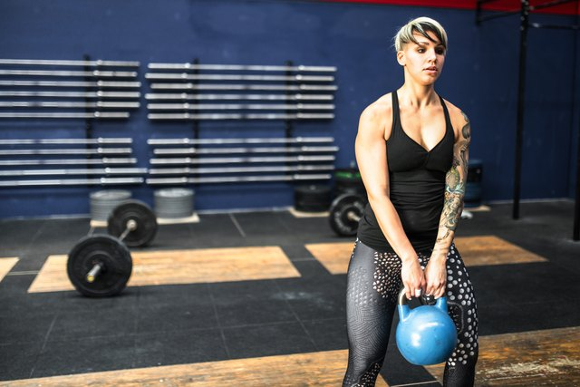 woman holding kettlebell in the gym to get lean
