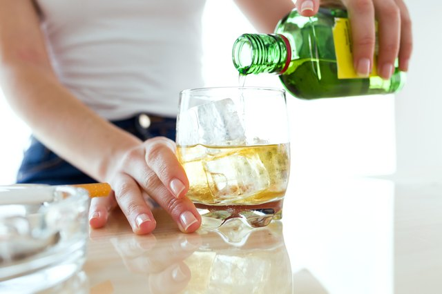 Young woman filling a glass of whiskey