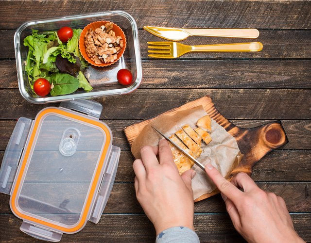 Woman preparing takeaway meal for her child. School lunch box with salad, fried chicken and nuts on rustic wooden background. Healthy eating habits concept.