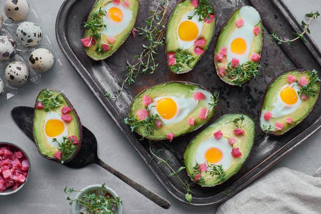 Keto diet dish: Avocado boats with ham cubes, quail eggs and cress sprout