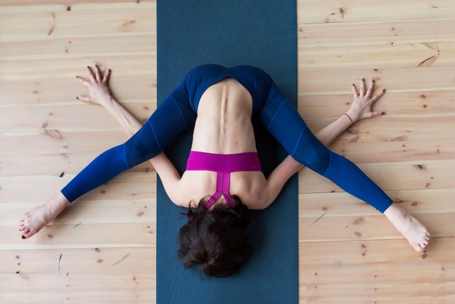 Top view of female yogi doing advanced kurmasana tortoise pose on mat indoors while practicing yoga