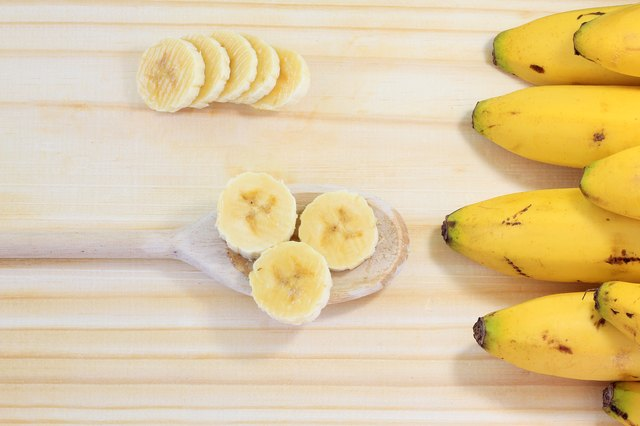 peeled banana on wood, sliced on wooden spoon, next to banana bunch, top view
