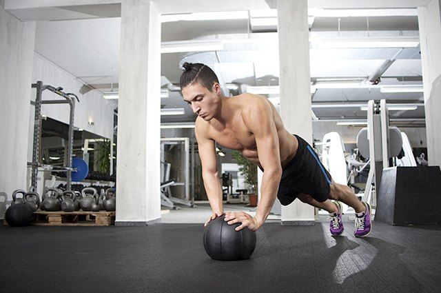 Man doing CrossFit workout on a medicine ball in a gym